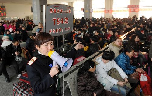 1月23日,在乌鲁木齐火车站候车室,一名工作人员在引导旅客候车.
