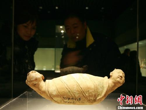 图为宋代双头人面首蛇身卧姿陶俑吸引民众驻足欣赏.