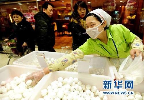 2月11日,工作人员将刚刚做好的手工元宵装袋销售.