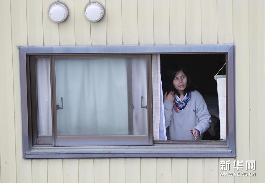 15日,在日本大地震重灾区宫城县石卷市,一名女子推开窗户,查看家乡