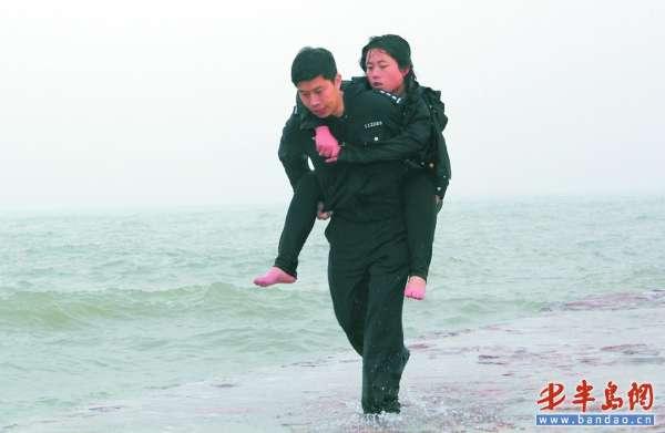 民警背起一名被救的落水女子朝沙滩走去