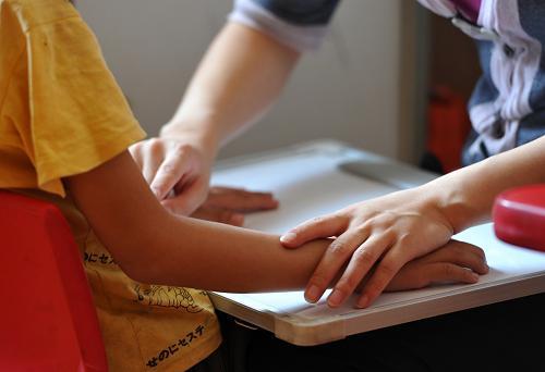 一名孤独症儿童的手,帮助孩子进行语言训练5月27日摄