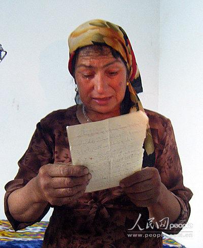 维吾尔族妇女帕塔木汗把多年所受庄院长的帮助用维语记在...