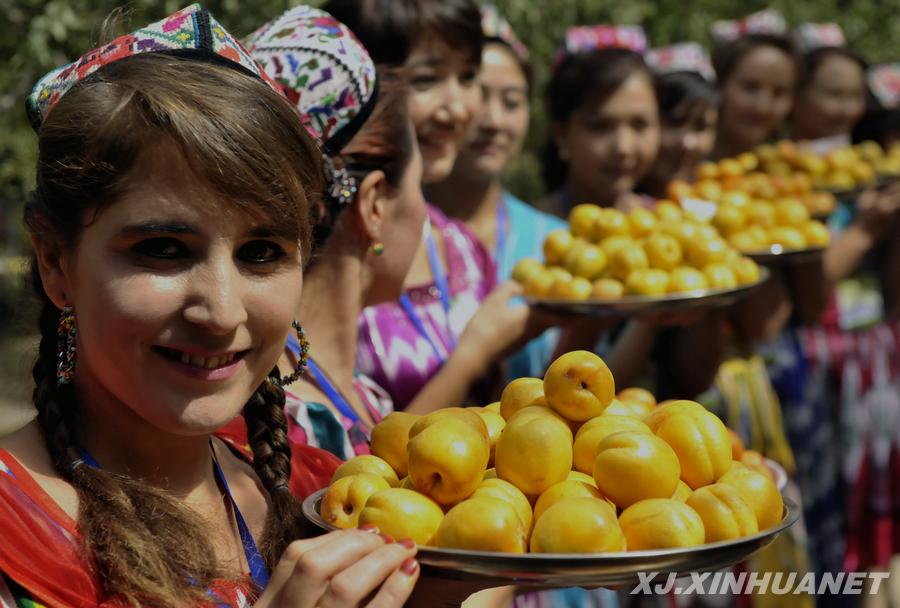 6月30日,来自各地的人们在英吉沙县的杏园里品尝鲜杏。
