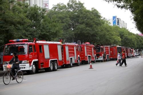 �7�8_警戒线外围满了围观的群众,交警忙着疏导交通秩序,路边停了七八辆供水
