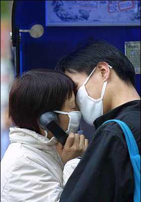 街头一对戴口罩的情侣在吻别