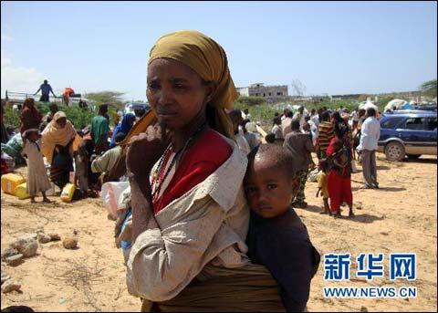 7月12日,在索马里首都摩加迪沙南部,一名妇女带着孩子抵达新建难民营。该难民营由索马里过渡政府为因大旱而流离失所的难民建立。